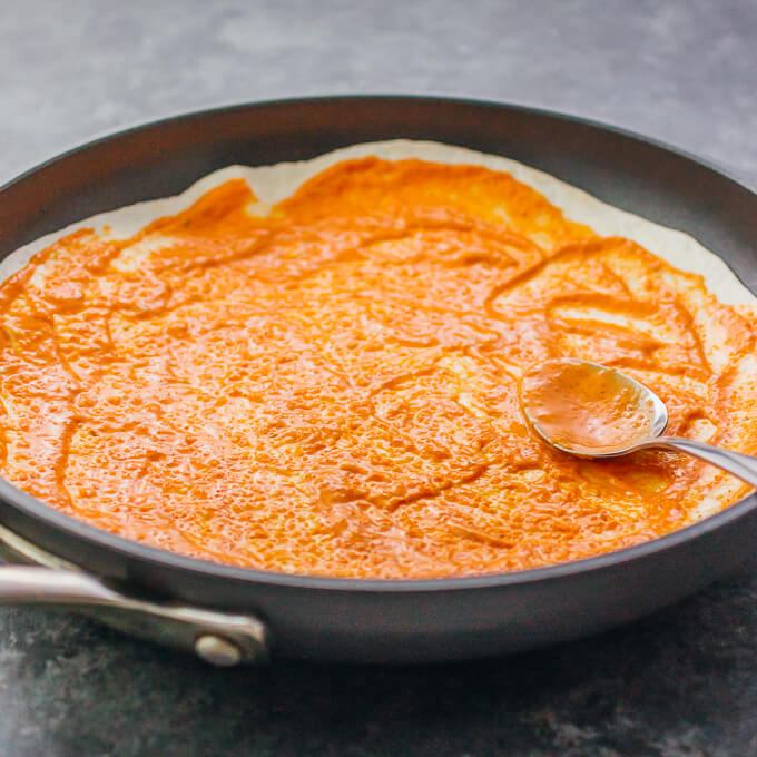 Spreading a spicy sauce over a tortilla in a pan