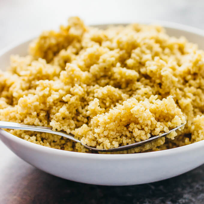 fluffing cooked couscous in white bowl
