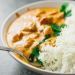 Brightly orange chicken tikka masala served in a white bowl garnished with cilantro