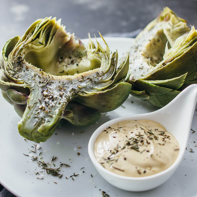 freshly cooked artichokes on white plate