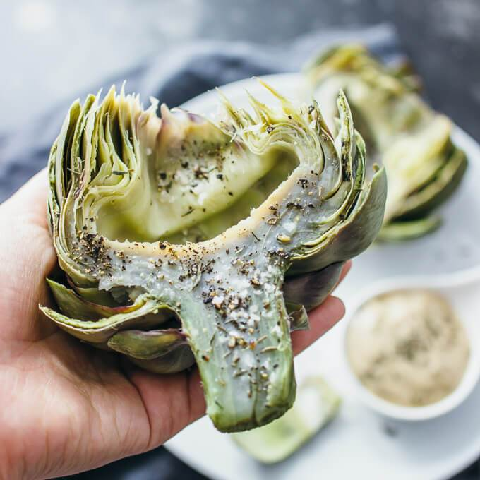 Trimmed and cooked artichoke in a hand, ready to be eaten