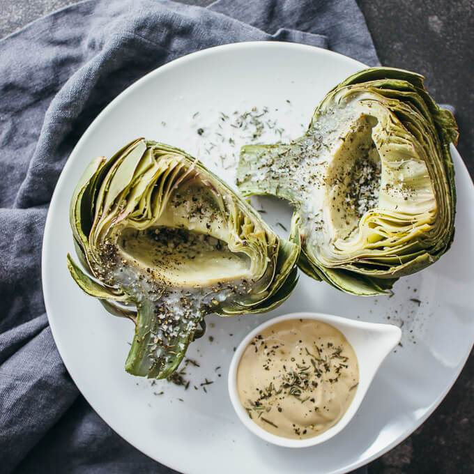 Overhead view of a white plate with healthy fresh artichokes cooked by boiling and served with a dipping sauce