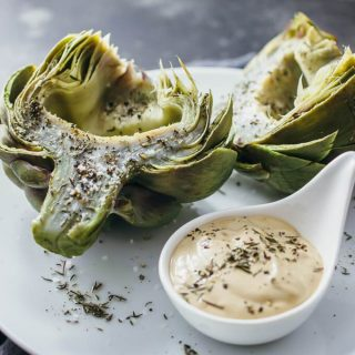 Freshly boiled and cooked artichokes including hearts served on a white plate with a mayo dipping sauce