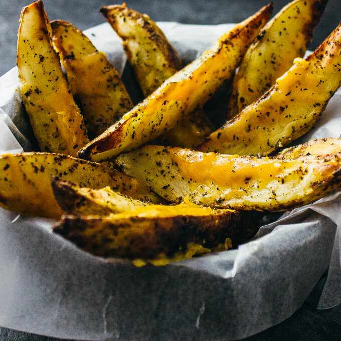 Baked potato wedges with melted cheddar cheese