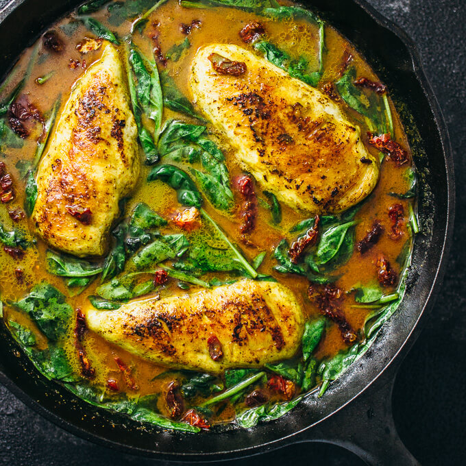 Chicken skillet with coconut milk curry and spinach in a cast iron pan