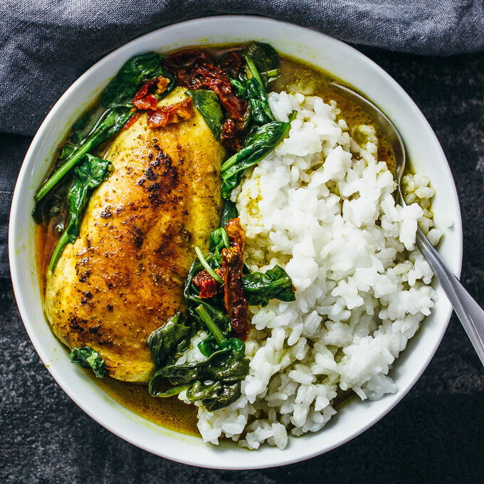 Overhead view of chicken and spinach in coconut sauce