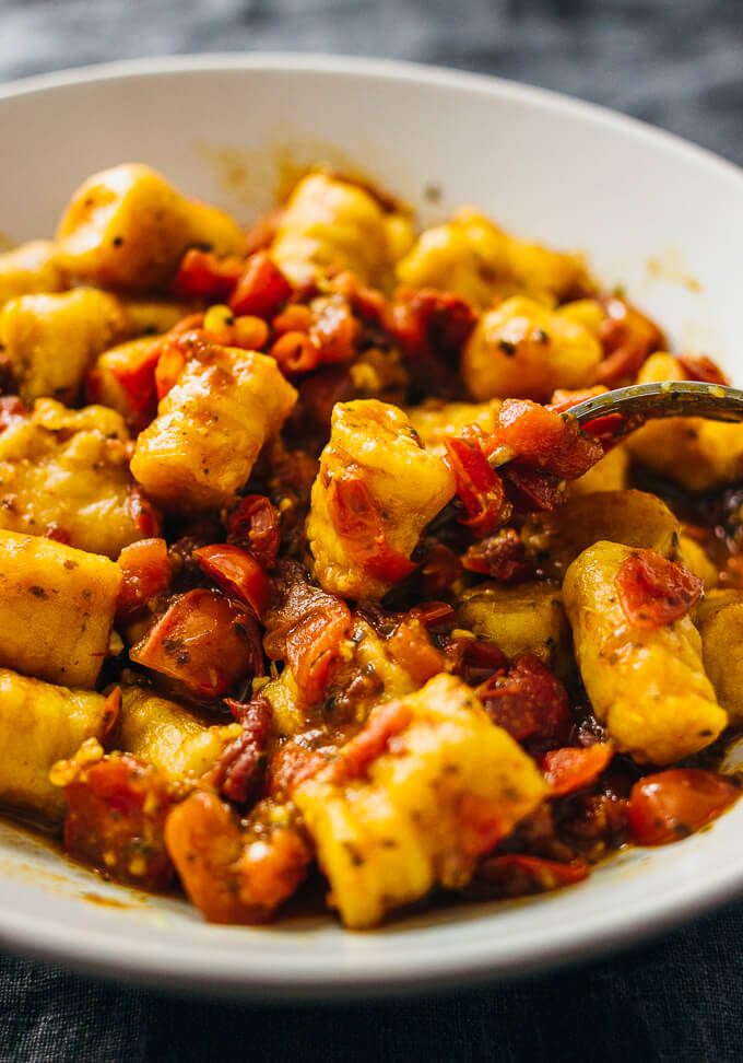 mixing sweet potato gnocchi with a spicy red sauce