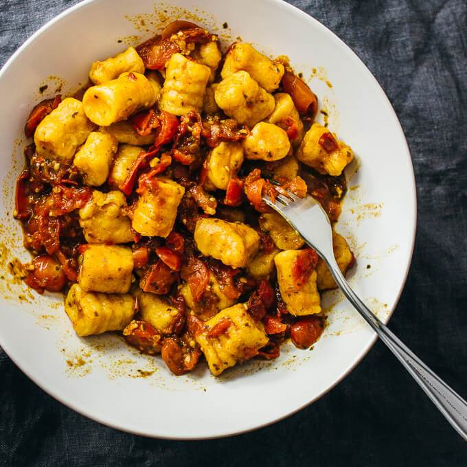 Homemade vegan sweet potato gnocchi with spicy red sauce in a white bowl