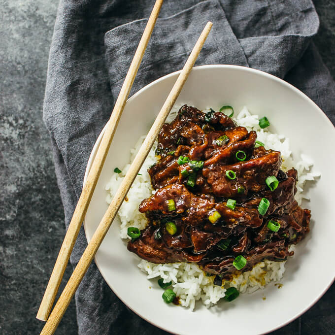 Mongolian beef similar to pf changs served with white rice in a white bowl