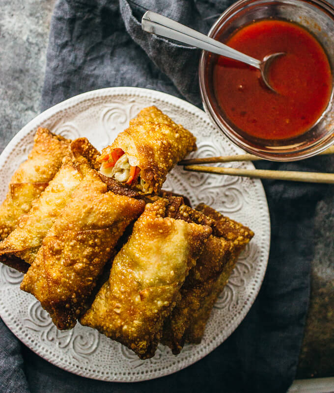 Vegetarian egg rolls on a white plate served with dipping sauce