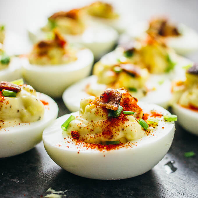 Spicy deviled eggs topped with bacon, chives, and paprika