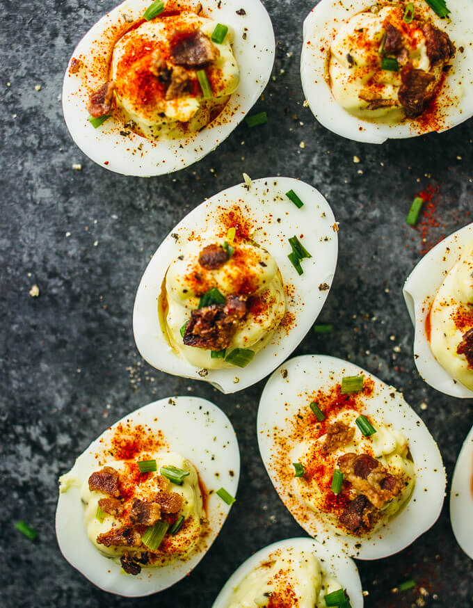 Spicy deviled eggs topped with crispy bacon, chives, and paprika