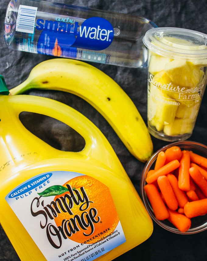 healthy pineapple smoothie ingredients like pineapples, carrots, banana, and orange juice