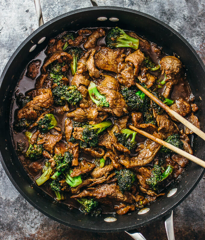Using chopsticks to easily stir flank steak and broccoli in a pan