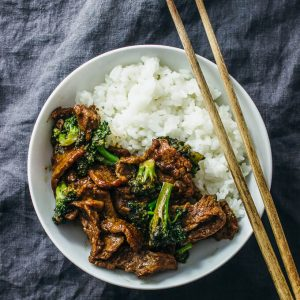 Easy beef and broccoli stir fry served with white rice in a white bowl