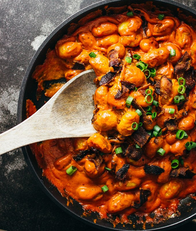 You'll love this spicy gnocchi arrabbiata pasta recipe with crispy crumbled bacon and sun-dried tomatoes simmered in a rich and creamy tomato sauce.