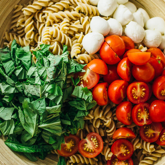 Easy caprese pasta salad with cherry tomatoes, mozzarella, and basil
