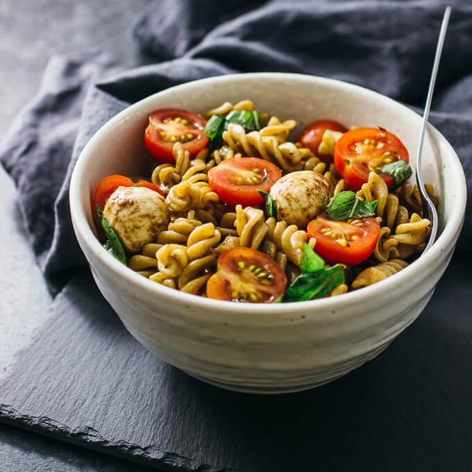 Easy caprese pasta salad with cherry tomatoes, mozzarella, and basil