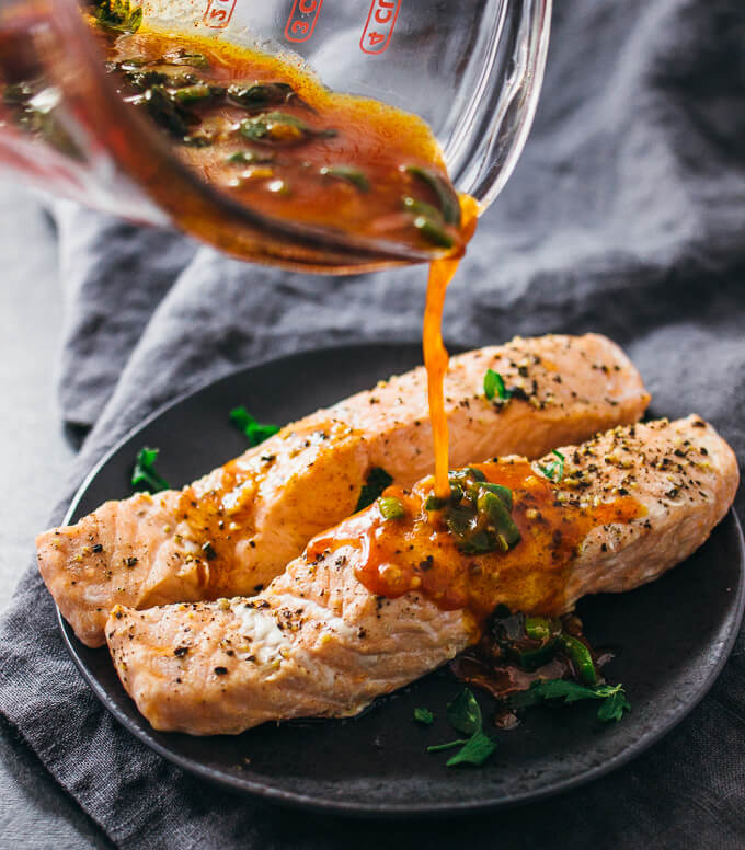 Pouring chili lime sauce on top of pressure cooked salmon