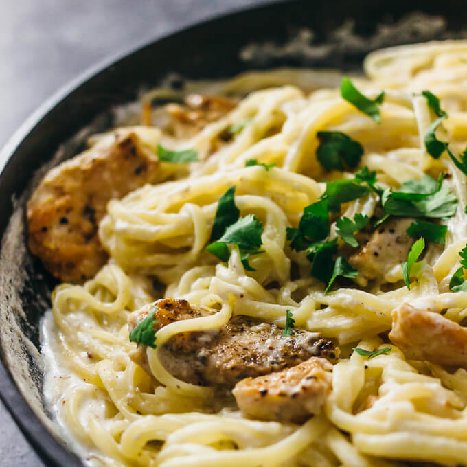 Alfredo spaghetti pasta with seared chicken and topped with green parsley