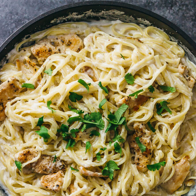 Chicken alfredo pasta with sauce in a black pan