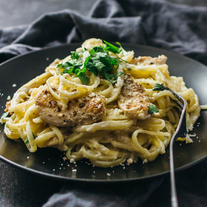 Lightened-up chicken alfredo pasta on a black plate