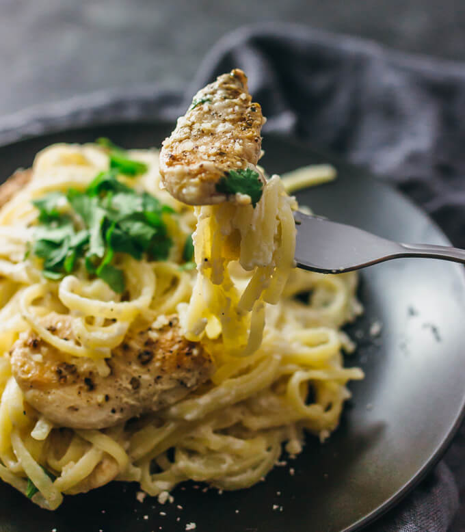 Picking up chicken alfredo pasta with fork