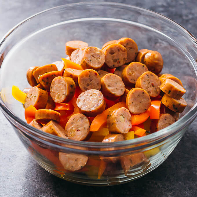 sliced sausage and bell peppers in a glass bowl