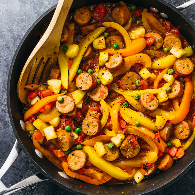 cooking sausage, peppers, peas, pineapples, and tomatoes in a pan