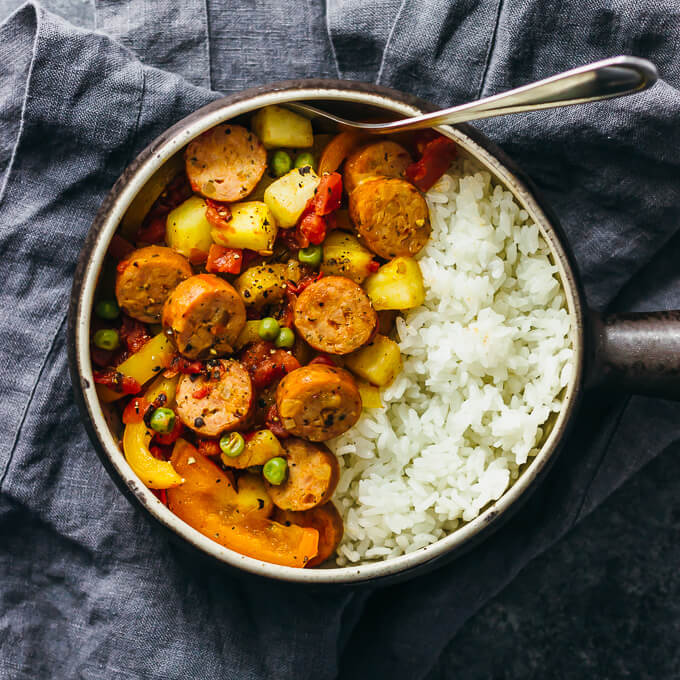 hawaiian sausage and peppers with rice in a bowl on a gray linen