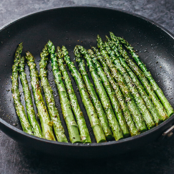 Asparagus spears cooking in a pan