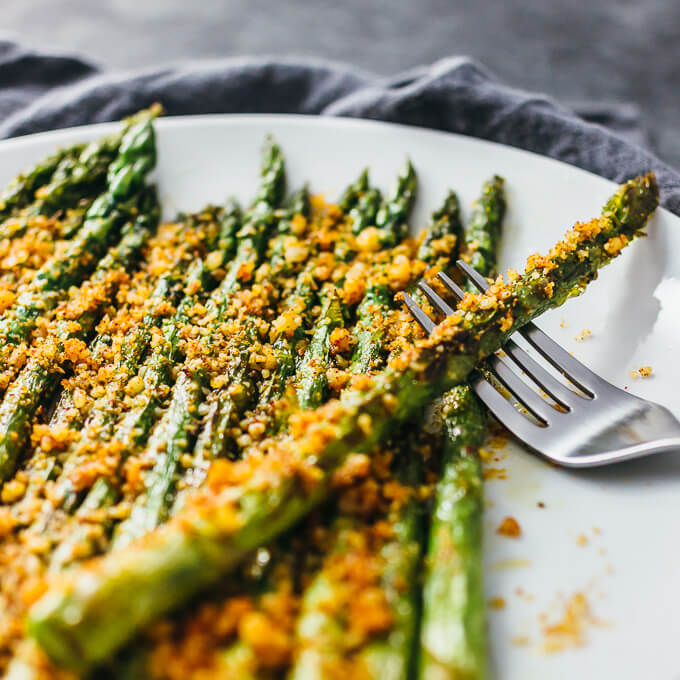 Cooked asparagus spears with parmesan on a white plate with fork