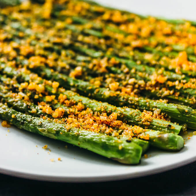 Parmesan cheese asparagus spears on a white plate