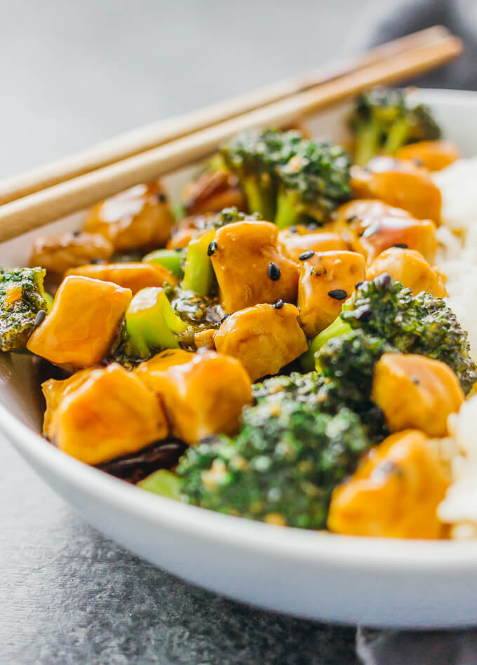 Teriyaki chicken rice bowl with broccoli in a white bowl with wooden chopsticks