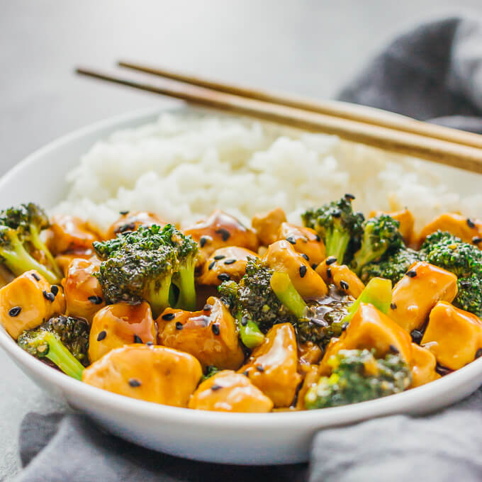 A teriyaki chicken bowl with broccoli and rice in a white bowl