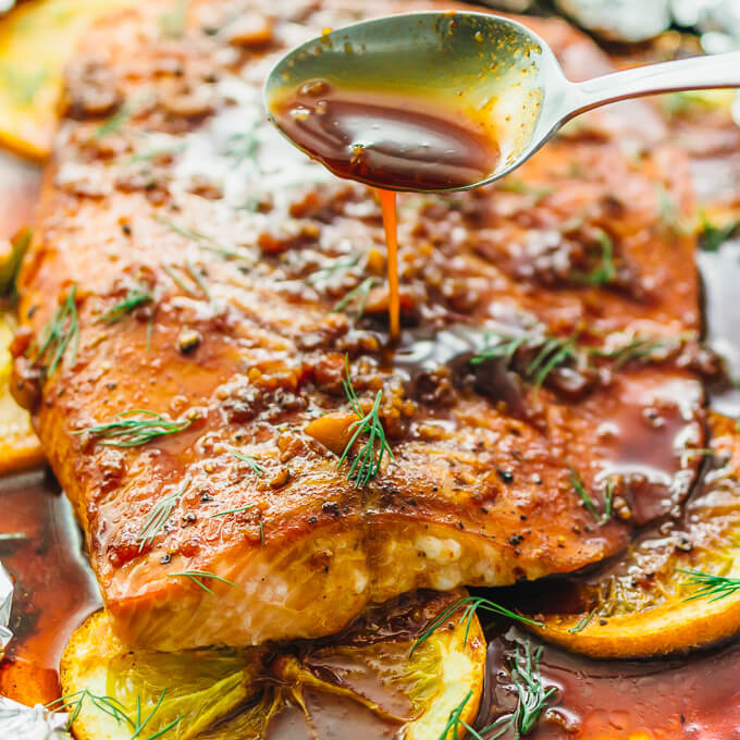 spooning sauce over baked salmon