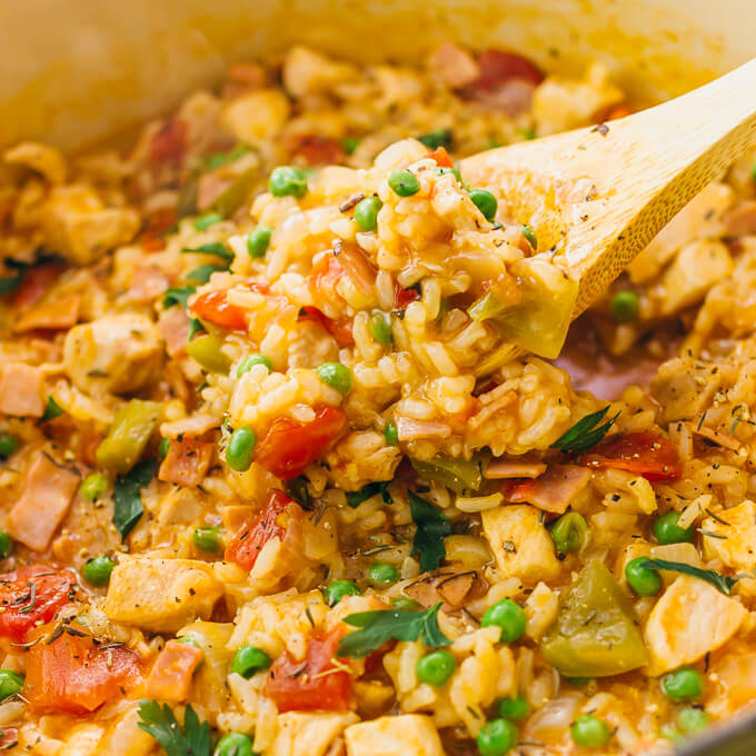 Wooden spoon scooping up chicken, rice, peas, and tomatoes