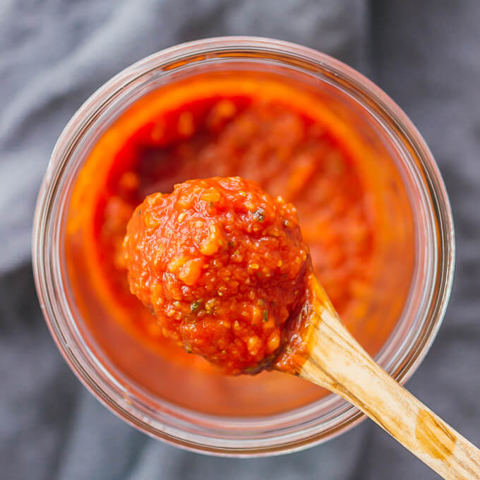 Pizza sauce in a glass jar lifted up by wooden spoon