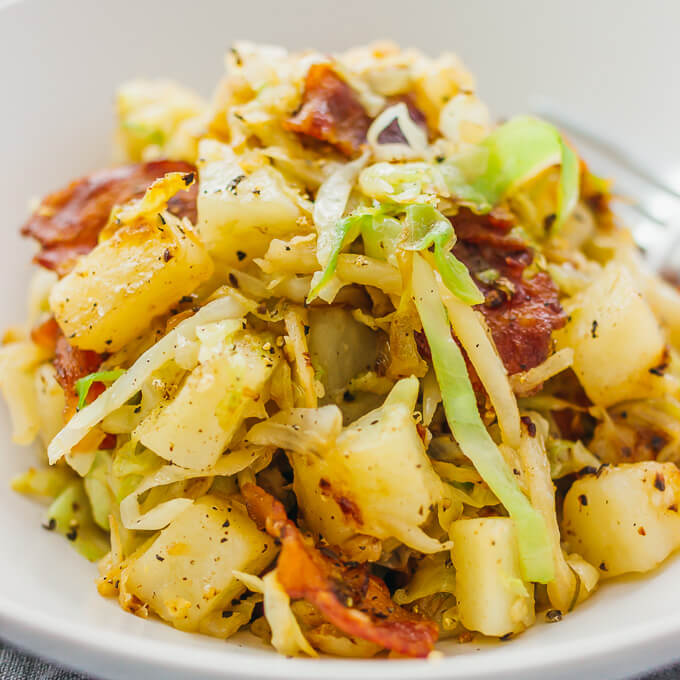 Fried cabbage and potatoes in a white bowl with bacon and pepper