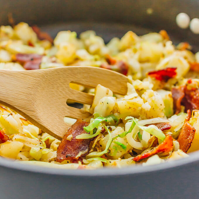Close up view of wooden spoon with fried cabbage and potatoes with bacon