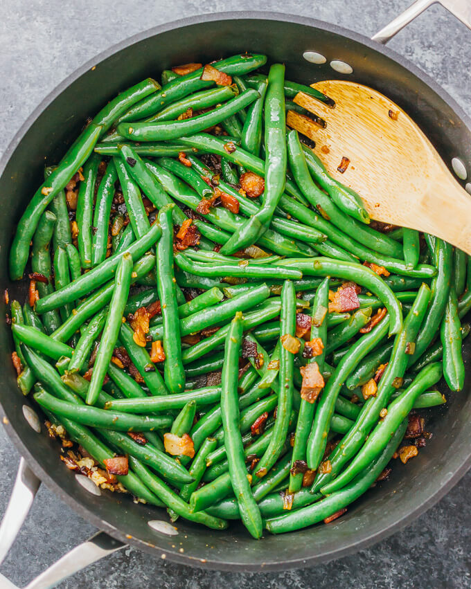Cooking green beans with bacon and garlic in a black nonstick pan