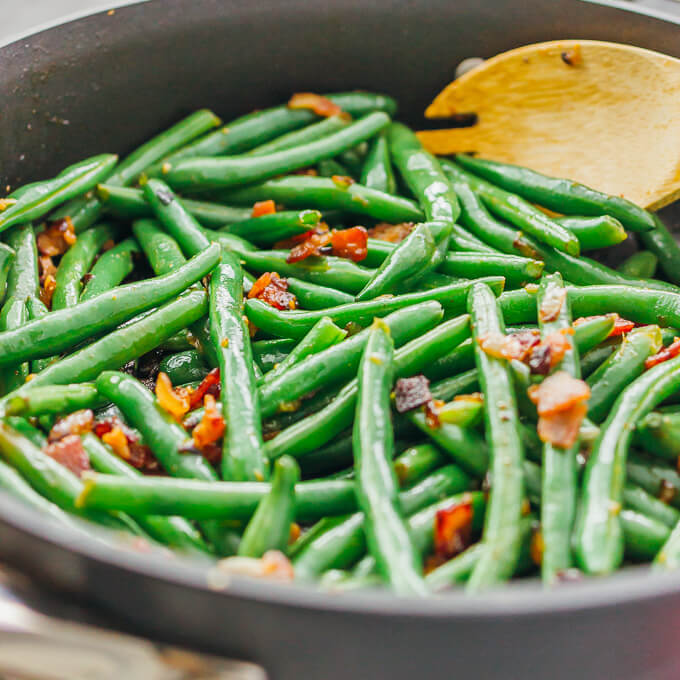 Side view of green beans cooking in a black pan with bacon bits