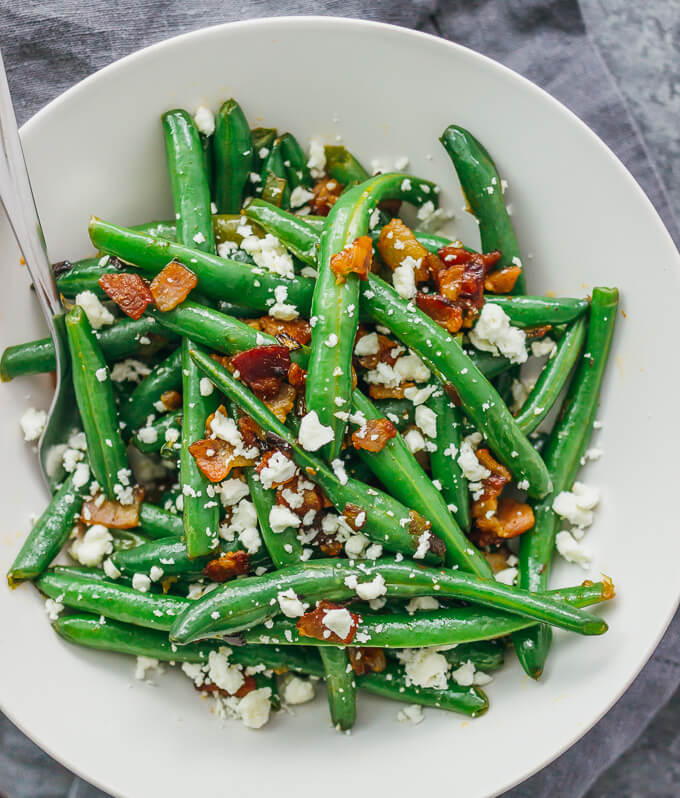 Garlic green beans served in a white bowl with feta cheese, bacon, and shallots