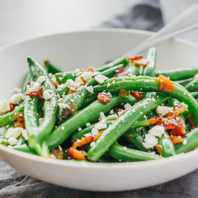 Cooked and sauteed green beans served with a fork in a white bowl