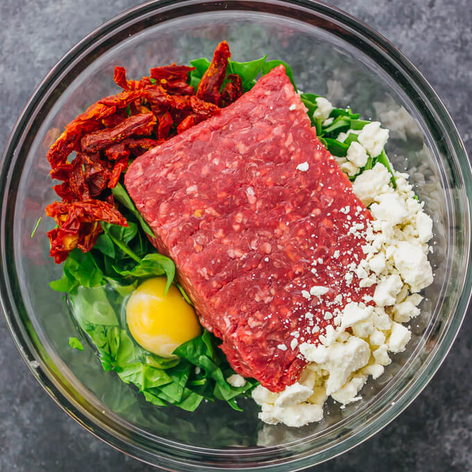 making greek burger meat by mixing ingredients in a glass bowl