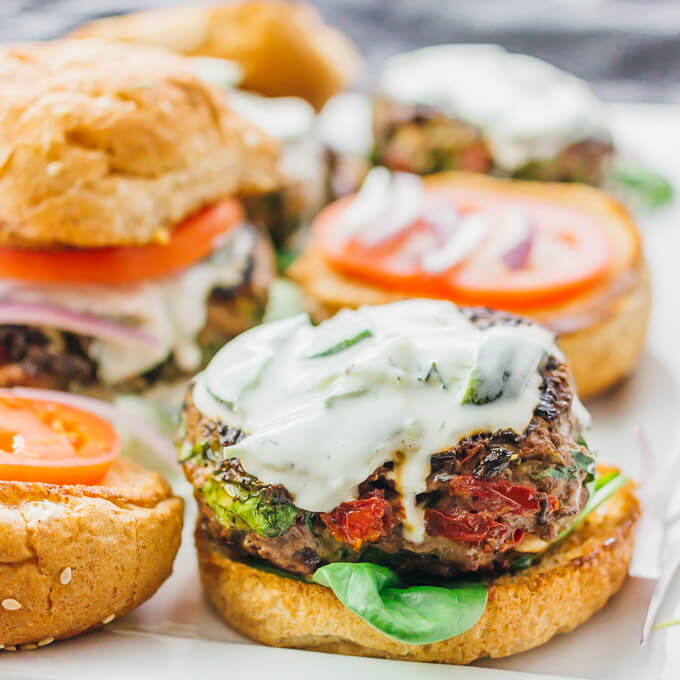 These Greek burgers are made using ground beef mixed with spinach, feta, and sun-dried tomatoes, plus drizzled with a delicious tzatziki sauce.