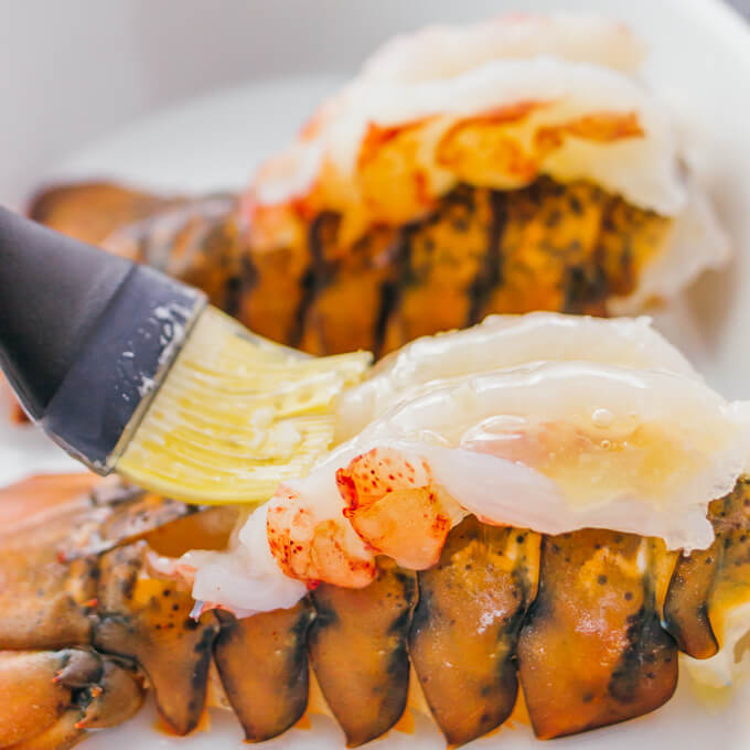 The best way to cook lobster tails, frozen or fresh, is by brushing with butter and broiling in the oven