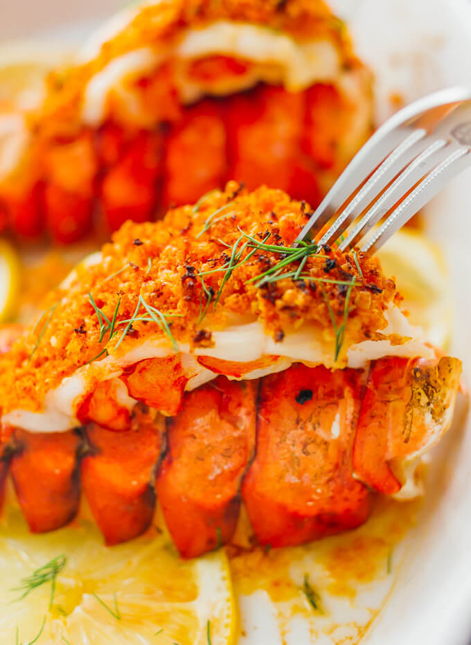 Broiled lobster tails are served with parmesan bread crumb topping