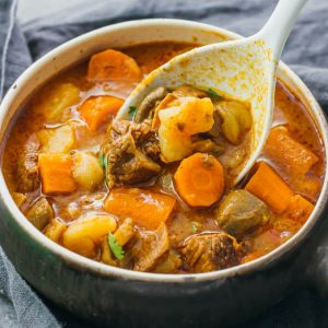 Serving instant pot beef stew with potatoes in a big bowl