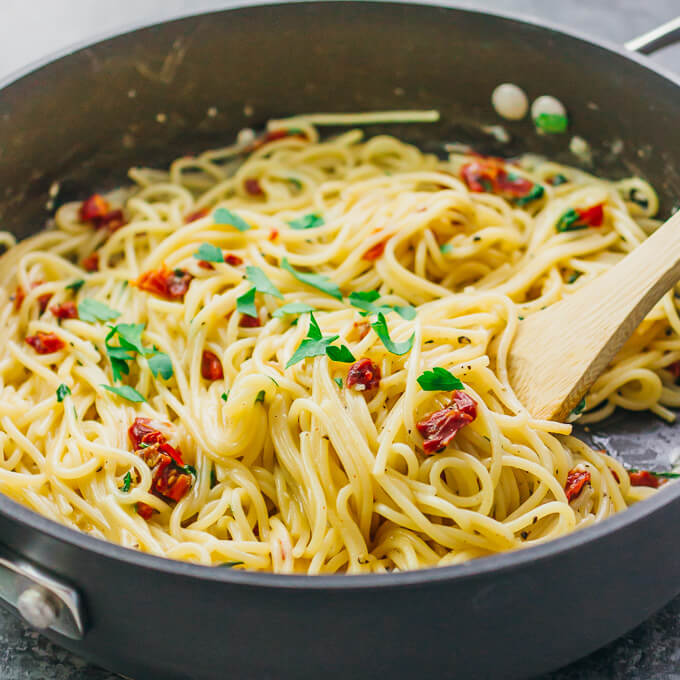 Stirring spaghetti aglio e olio in a black pan with sun dried tomatoes